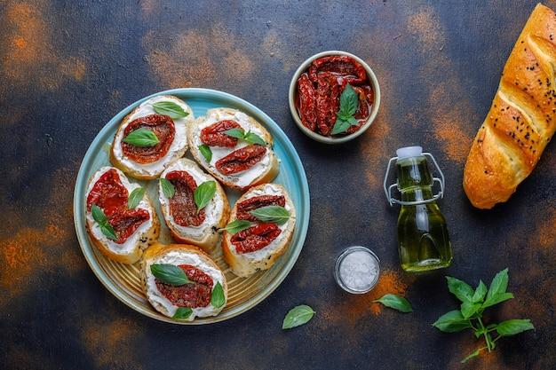 Italienische sandwiches - bruschetta mit käse, trockenen tomaten und basilikum