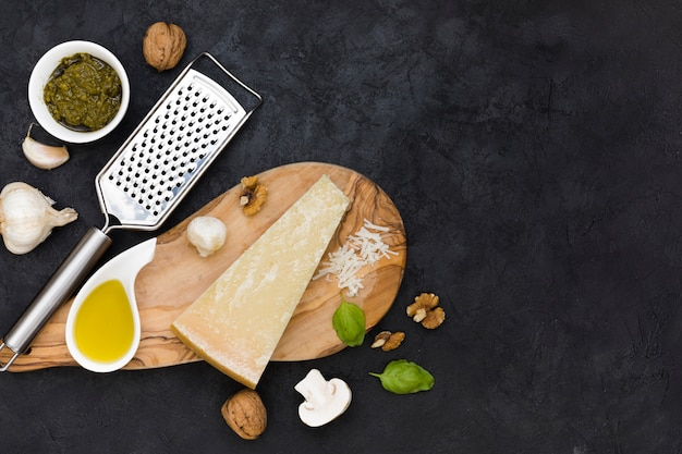Italienische sauce; käseblock; olivenöl; nussbaum; knoblauchzehe; basilikum und pilz auf edelstahlreibe