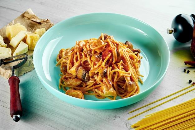 Italienische spaghetti-nudeln mit roter sauce, hühnchen, pilzen und parmesan, serviert in einem blauen teller auf einem holztisch. restaurant essen.