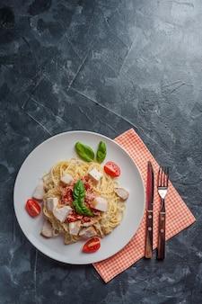 Italienische spaghetti-nudeln mit sauce und hühnchen, käse-parmesan und basilikum