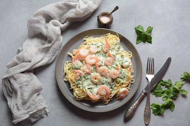Italienische spaghetti oder pasta mit garnelen, knoblauch und kräutern in cremiger sauce.
