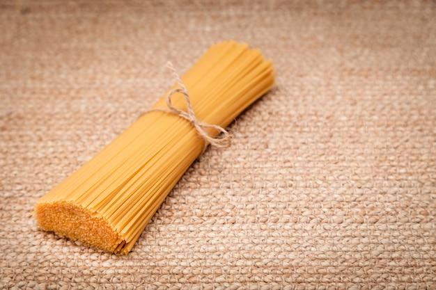 Italienische spaghettiteigwaren gebunden im bündel durch das handwerksseil, das an der natürlichen oberfläche liegt