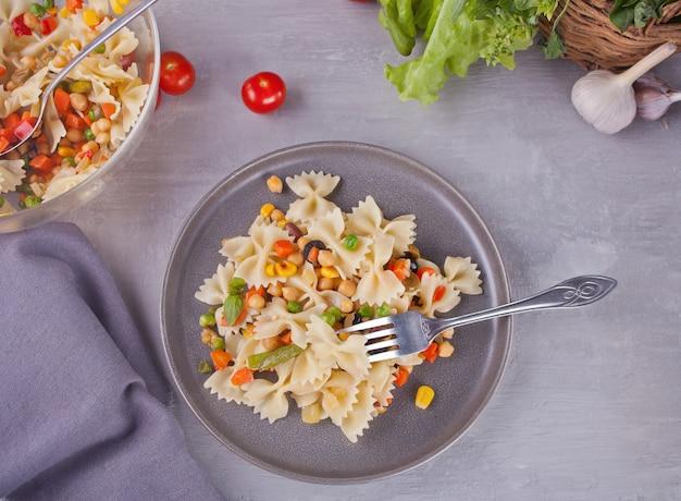 Italienische teigwaren farfalle mit mischungsgemüse auf einer grauen platte auf einem grauen hintergrund. draufsicht