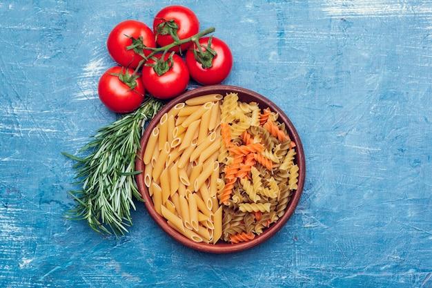 Italienische teigwaren in der platte auf blauem holztisch