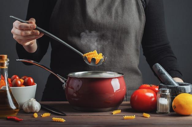 Italienische teigwaren in einem topf in der küche kochen.