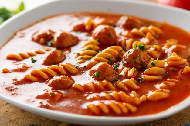 Italienische tomatensuppe mit nudelnudeln und fleischbällchen auf teller serviert.