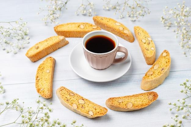 Italienische toskanische traditionelle kekse cantuccini mit mandeln, eine tasse kaffee auf licht