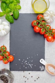 Italienische, traditionelle caprese-salatzutaten mit kirschtomaten, mozzarella und basilikum.