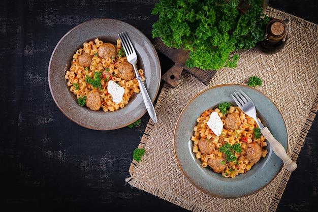 Italienische traditionelle ditalini-nudeln mit fleischbällchen in tomatensauce und gemüse in einer schüssel. ditalini-nudeln und rindfleischbällchen mit marinara-tomatensauce. ansicht von oben. flach liegen.
