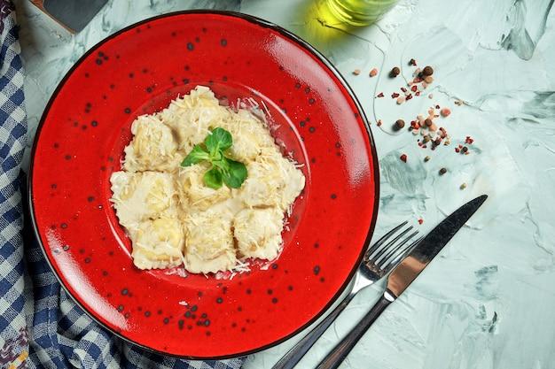 Italienische traditionelle ravioli mit hackfleisch in einer cremigen nusssauce in einem weißen teller