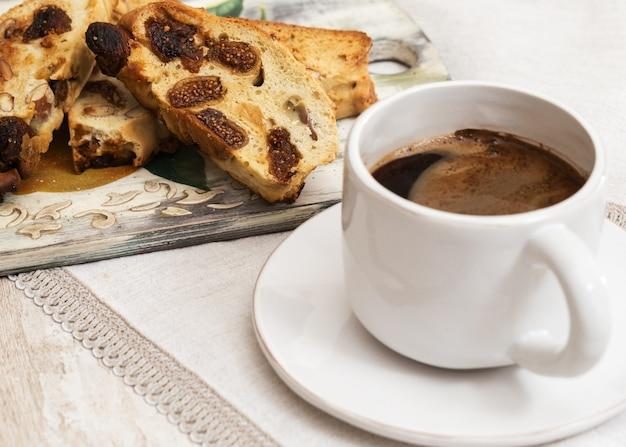 Italienische trockene kekse biscotti auf hölzernem schreibtisch. cantucci und kaffee zum frühstück. selektiver fokus. speicherplatz kopieren.