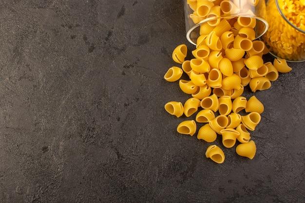 Italienische trockene nudelgelb rohe innenschale der vorderansicht lokalisiert auf dem dunklen hintergrund italienisches nudelnahrungsmittelmehl