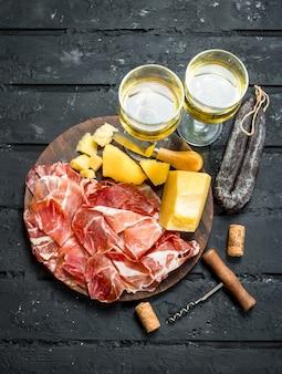 Italienische vorspeisen mit weißwein. auf schwarzer rustikaler oberfläche.