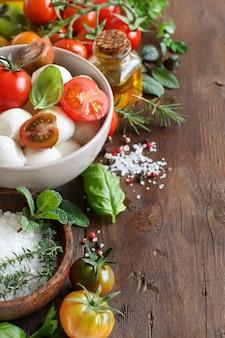 Italienische zutaten für caprese-salat auf holztisch hautnah