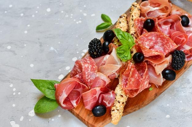 Italienischer antipasti-schinken, salami, bresaola-oliven, tomaten und grissini-brotstangen. aperitif happy hour