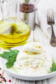 Italienischer burrata-frischkäse mit olivenöl, frischem rucola, rosa, grünem und schwarzem pfeffer
