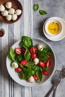 Italienischer caprese-salat mit geschnittenen tomaten, mozzarella, basilikum, olivenöl auf grauem hintergrund