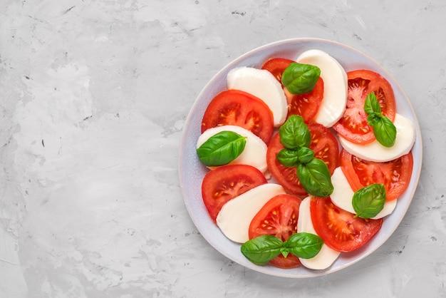 Italienischer caprese-salat mit geschnittenen tomaten, mozzarella, basilikum, olivenöl in einem teller