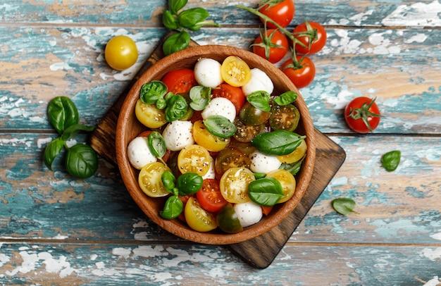 Italienischer caprese-salat mit geschnittenen tomaten, mozzarella, basilikum, olivenöl in holzschale.