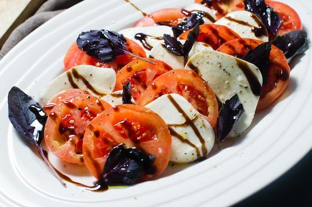 Italienischer caprese-salat. zutaten mozzarella, tomaten, basilikum, salz, pfeffer, balsamico.