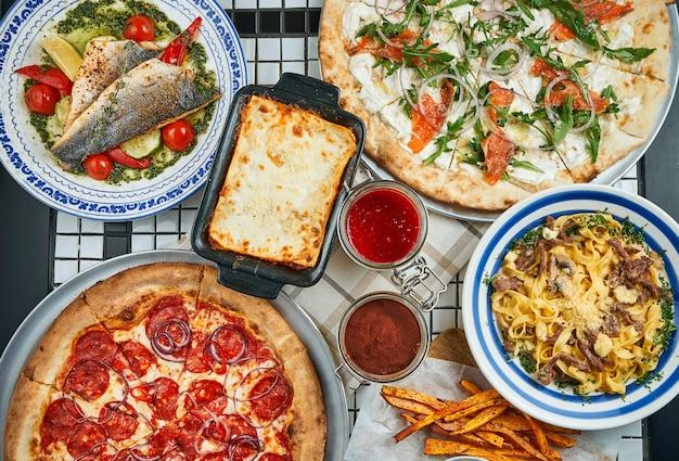 Italienischer esstisch mit pizza, pasta, gebackenem wolfsbarsch, lasagne und desserts. draufsicht essen flach liegen.
