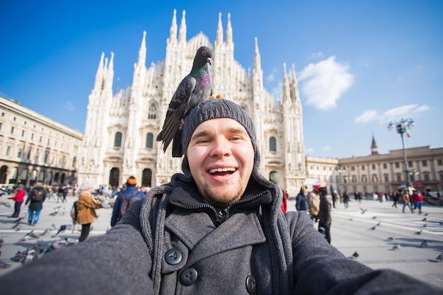 Italienischer exkursions- und reisekonzept lustiger kerl, der selfie mit tauben vor dem dom der kathedrale nimmt
