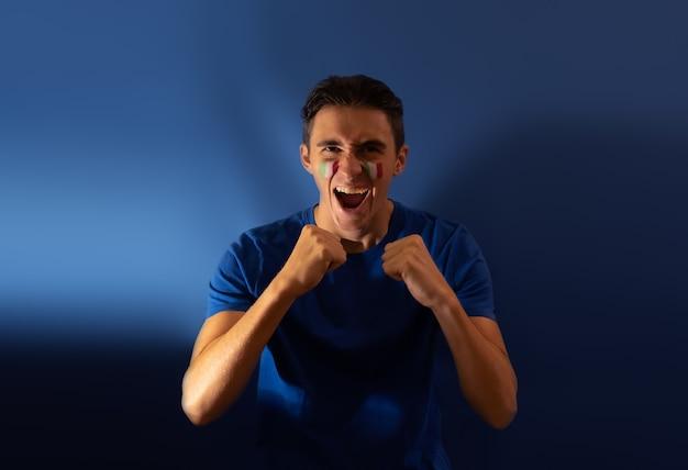 Italienischer fußballfan schreit nach seiner nationalmannschaft auf blauem hintergrund flagge über gesicht gemalt
