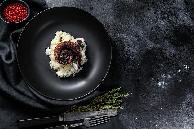 Italienischer klassiker risotto mit tintenfischtentakeln. schwarzer hintergrund