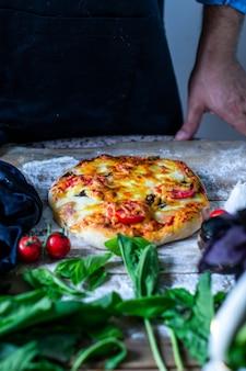 Italienischer koch, der pizzamannhände kocht, kocht pizzateig für pizza