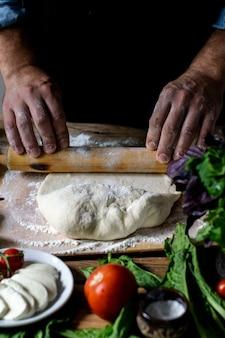 Italienischer koch kocht pizzamannhände, die pizzateig für pizzahände des kochkochs kochen