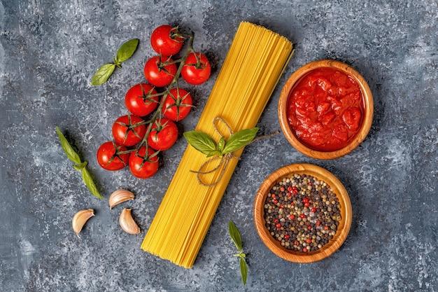 Italienischer lebensmittelhintergrund mit nudeln, gewürzen und gemüse.