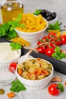 Italienischer lebensmittelhintergrund mit rohen nudeln, tomaten, oliven und mozzarella