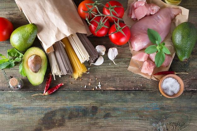 Italienischer lebensmittelhintergrund mit tomaten, basilikum, spaghetti, oliven, knoblauch