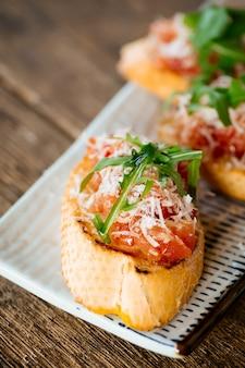 Italienischer parmesan-rucola mit bruschetta-tomaten