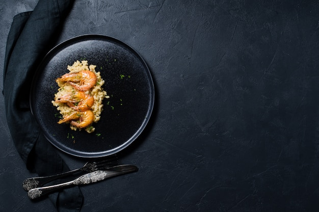 Italienischer risotto mit garnele auf einem schwarzblech.