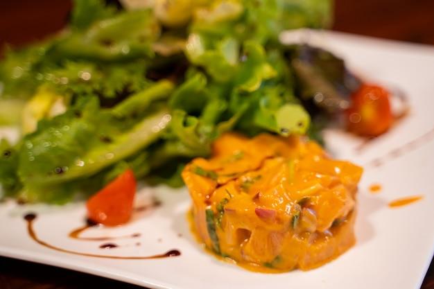 Italienischer roher lachssalat auf der weißen platte