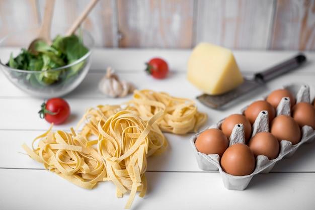 Italienischer roher lebensmittelbestandteil und braunes ei über hölzerner planke