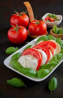 Italienischer salat antipasti namens caprese mit büffelmozzarella, tomate und basilikum mit olivenöl