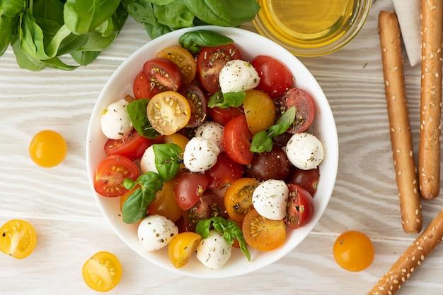 Italienischer salat mit kirschtomaten, mozzarella und basilikum