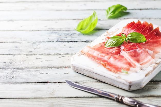 Italienischer schinken-crudo oder jamon mit basilikum auf schneidebrett über holz.