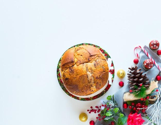 Italienischer schokoladenpanettone weihnachtskuchen mit flitterdekorationen, kerzen, kiefernkegel ,.