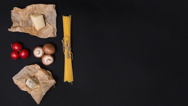 Italienischer spaghettiteigwarenbestandteil mit kopienraum auf schwarzer oberfläche