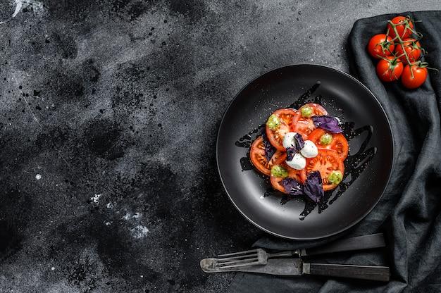 Italienischer traditioneller caprese-salat. kirschtomaten, mozzarella, basilikum, pesto-sauce. draufsicht. speicherplatz kopieren