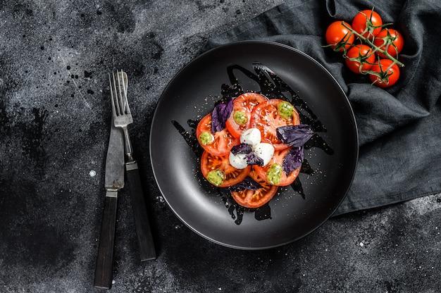 Italienischer traditioneller caprese-salat. kirschtomaten, mozzarella, basilikum, pesto-sauce. schwarzer hintergrund. draufsicht