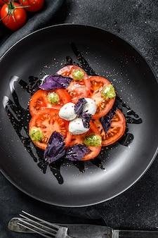Italienischer traditioneller caprese-salat. kirschtomaten, mozzarella, basilikum, pesto-sauce