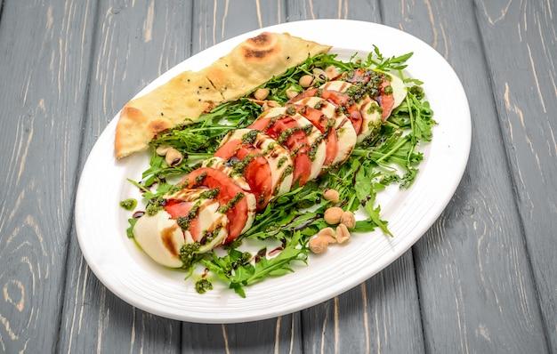 Italienischer traditioneller caprese salat mit pestosoße und basilikum