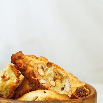 Italienischer trockener keksbiscottiabschluß oben mit nüssen in einer hölzernen schüssel.