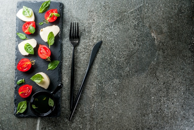 Italienisches abendessen. hausgemachter salat caprese - tomaten, frisches basilikum, mozzarella, olivenöl. auf einem schwarzen steintisch. am spieß serviert. kopieren sie die draufsicht des raumes