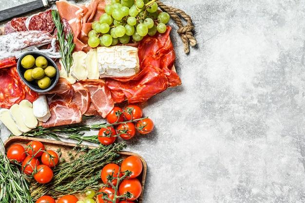 Italienisches antipasti, holzschneidebrett mit schinken, schinken, parma, ziege und camembertkäse, oliven, trauben. antipasti. draufsicht