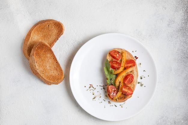 Italienisches bruschetta mit tomaten auf einer weißen platte gegen weißen hintergrund. von oben betrachten